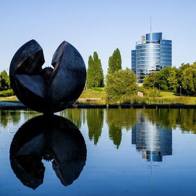 Stuttgart, runde Statue im Wasser vor einem Park und Gebäude