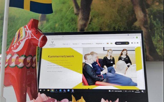 Laptop mit Dalahäst, Schwedenfahne und Blumenkranz